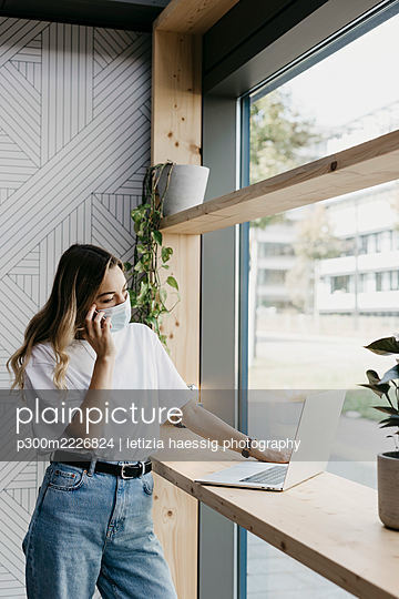 Woman wearing protective face mask while talking on smart phone using laptop standing in cafe during covid-19 - p300m2226824 by letizia haessig photography