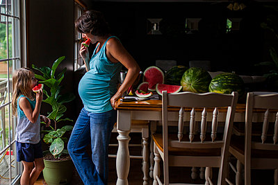 Mother and daughter eating watermelon at home - p1166m1176276 by Cavan Images