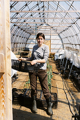 A young female farmer working in green house in the morning in spring - p1166m2269688 by Cavan Images