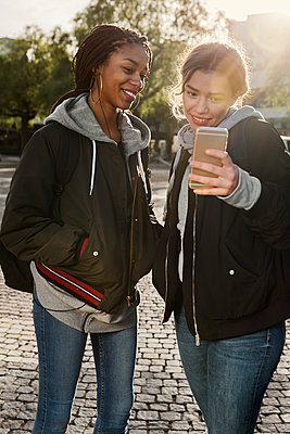 Teenage girls using smart phone - p352m2121193 by Folio Images