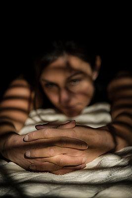 Junge Frau liegt mit gefalteten Händen auf dem Bett - p397m1556580 von Peter Glass