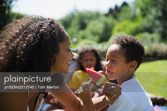 Playful mother and son eating watermelon popsicles on sunny patio - p1023m2212740 by Tom Merton