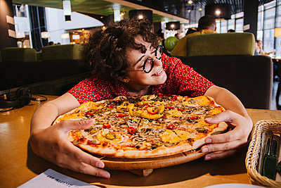 Happy woman holding pizza on wooden table while sitting in restaurant - p1166m2105681 by Cavan Images