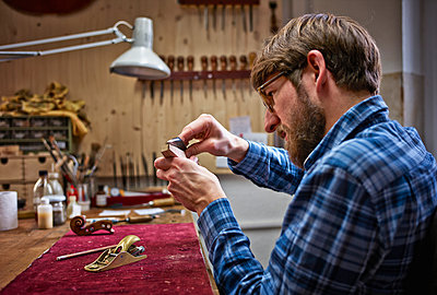 Violin maker in his workshop examining neck of an instrument - p300m926381f by Dirk Kittelberger