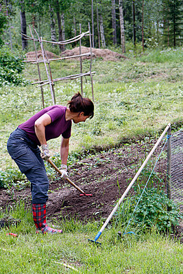 Woman working in garden - p312m799255f by Håkan Hjort