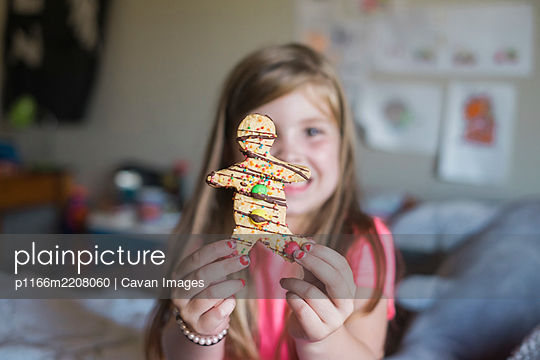 Young girl holding a gingerbread man sitting in her bedroom - p1166m2208060 by Cavan Images