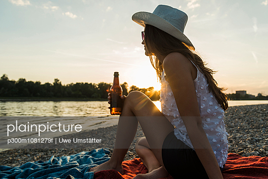 Young woman drinking beer at the riverside at sunset - p300m1081279f by Uwe Umstätter