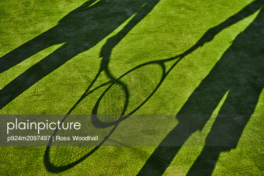 Cropped shadows of two tennis players with tennis rackets on green lawn - p924m2097497 by Ross Woodhall