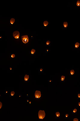 Low angle view of illuminated Chinese lanterns flying against sky at night - p1166m2112249 by Cavan Images