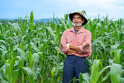 Elderly asian man in a shirt standing at corn field in sunny day - p1166m2269507 by Cavan Images