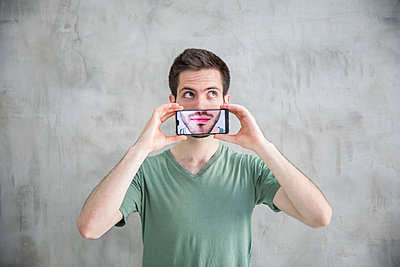 Young man is holding smartphone with his mouth on the display - p276m2110765 by plainpicture