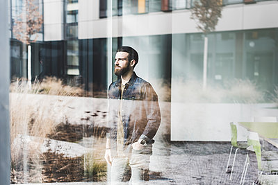 Young businessman standing at window pane, wearing smart watch - p300m1356515 by Uwe Umstätter