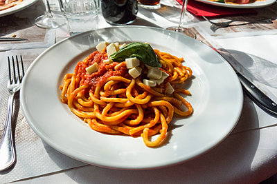 Plate of spaghetti with tomato sauce on restaurant table - p429m1198314 by Seb Oliver