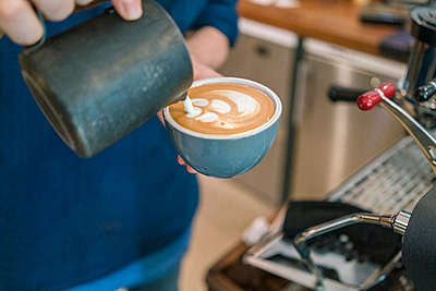 Close up of a jug of milk being poured into a cup of coffee by a barista. - p429m2182833 by Tamboly
