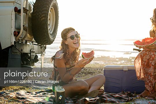 Happy female friends eating watermelon at beach against clear sky - p1166m1226180 by Cavan Images