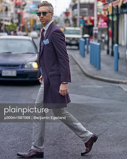 Portrait of fashion blogger Steve Tilbrook walking in the city - p300m1587068 von Benjamin Egerland