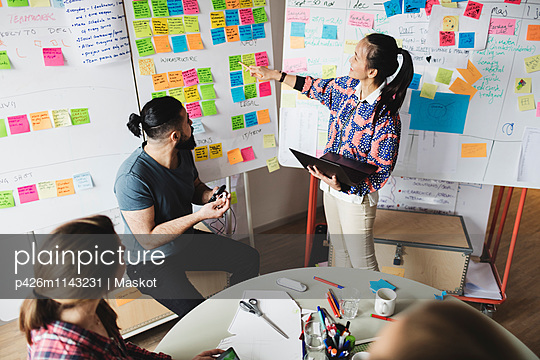 High angle view of businesswoman showing notes and explaining colleagues during meeting