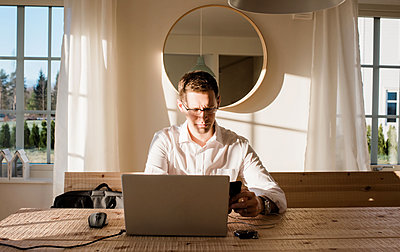 Man working from home looking at his phone and laptop concentrating - p1166m2148548 by Cavan Images