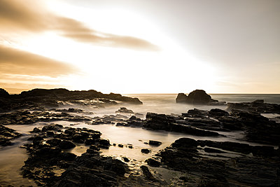 Long Exposure, Sea, Evening Light with Moody Clouds & Rugged Rocks - p1166m2212362 by Cavan Images
