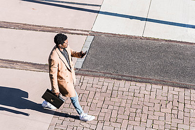 Businessman walking outdoors with briefcase, cell phone and earphones - p300m1568540 by Uwe Umstätter