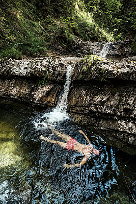 Germany, Upper Bavaria, Bavarian Prealps, lake Walchen, young man is swimming in a plunge pool - p300m2083949 by Wilfried Feder