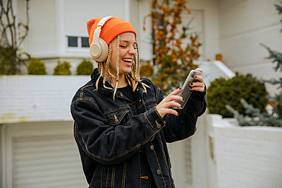 Portrait of a blonde girl with braids and blue eyes wearing a hat listening to music with the mobile phone and headphones. Lleida, Spain. - p300m2242258 von Aitor Carrera Porté