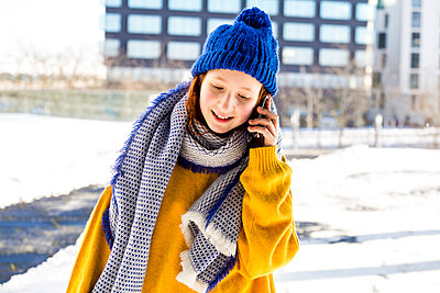Girl in warm clothing talking on mobile phone against building - p300m2265809 by Irina Heß