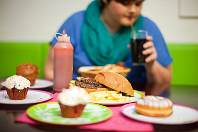 Young woman in cafe with table of food - p429m824216f by Zero Creatives