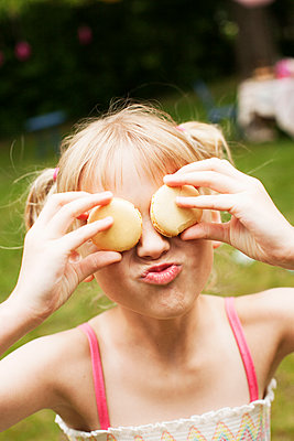 Close up of girl holding cookies over eyes in backyard - p555m1409064 by Shestock