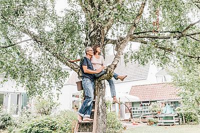 Reifes Paar klettert auf einen Baum - p586m1178400 von Kniel Synnatzschke