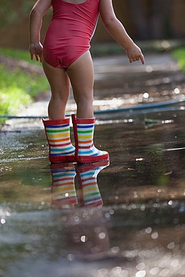 Child in wellies playing in puddle of water - p924m1125790f by Kinzie Riehm