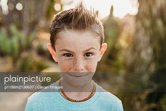 Close up portrait of cute young boy with freckles making serious face - p1166m2136637 by Cavan Images