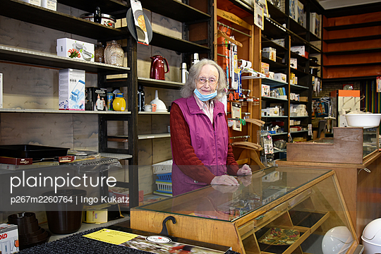 Old saleswoman with mouth protection in her shop - p267m2260764 by Ingo Kukatz
