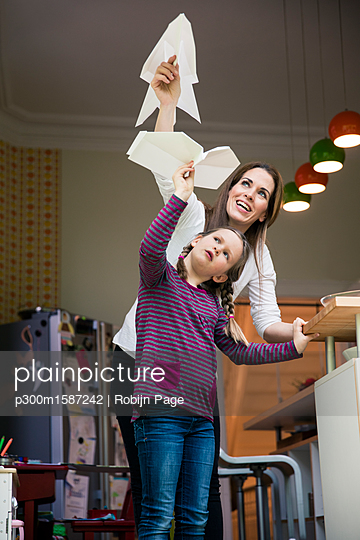 Happy mother and daughter throwing paper plane together at home - p300m1587242 von Robijn Page
