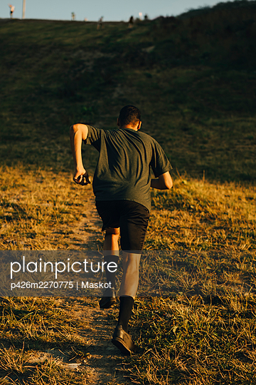 Rear view of male athlete running on land during sunset - p426m2270775 by Maskot