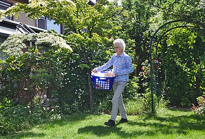 Ältere Frau mit Wäschekorb - p1231m2093376 von Iris Loonen