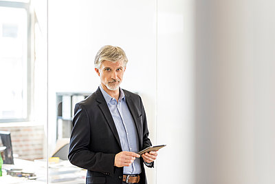 Mature man standing in his office, using didgital tablet - p300m1587213 von Jo Kirchherr