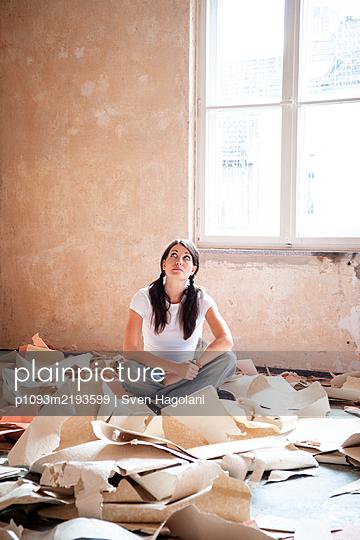 Junge Frau sitzt zwischen Tapetenresten - p1093m2193599 von Sven Hagolani