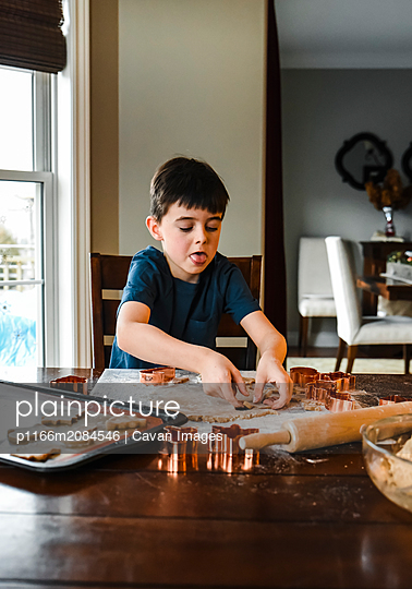 Young boy making cookies with cookie cutters at the table. - p1166m2084546 by Cavan Images