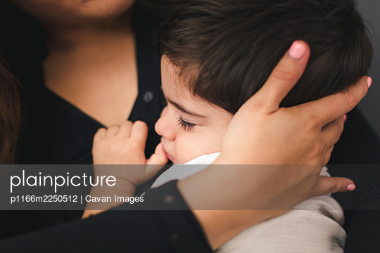 Mother holding son's head while he sleeps. - p1166m2250512 by Cavan Images