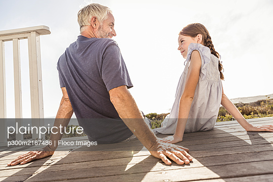 Father and daughter sitting on terrace in sunshine - p300m2167486 by Floco Images