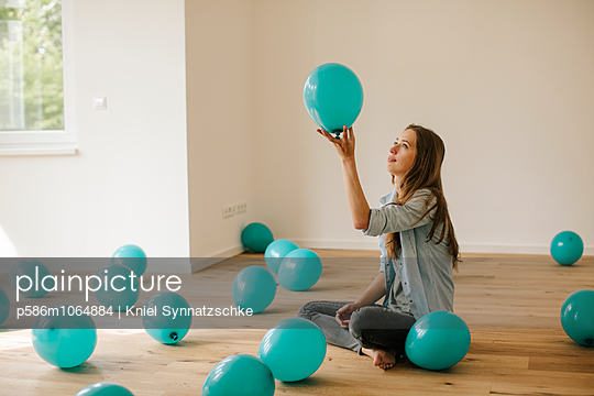 Young woman in new apartment playing with balloons - p586m1064884 by Kniel Synnatzschke