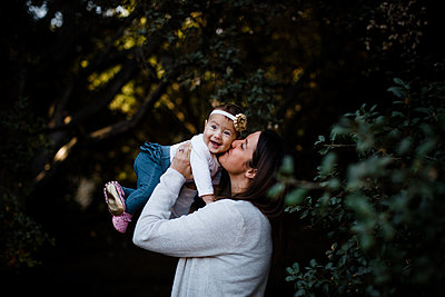 Mom Kissing Daughter as Baby Smiles - p1166m2146350 by Cavan Images