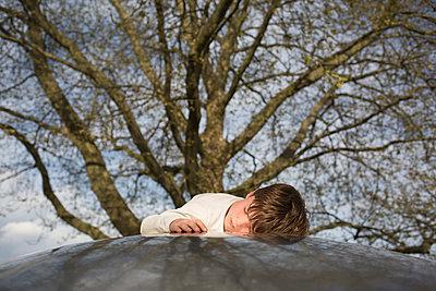 Junge liegt vor Baum - p1308m2247488 von felice douglas
