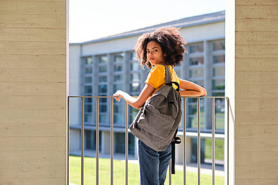 Student with bag staring while leaning on railing at university - p300m2242328 by Antonio Ovejero Diaz
