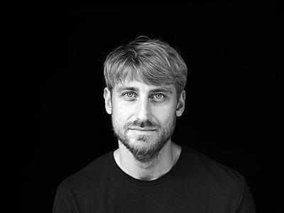 Handsome mid adult man against black background - p300m2274504 by Jo Kirchherr