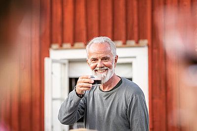 Smiling man having red wine - p312m2208234 by Plattform