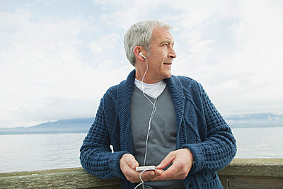 Profile of middle-aged man on dock listening to music. - p328m784076f by Hero Images