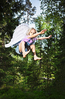 Girl wearing wings and jumping in forest - p42916136f by Christoffer Askman