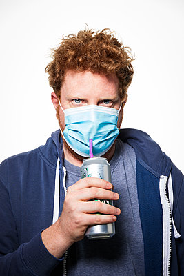 Man with surgical mask and beverage, portrait - p930m2253759 by Ignatio Bravo